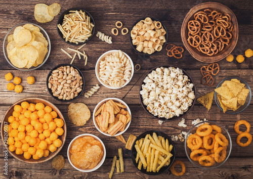 Fotografía All classic potato snacks with peanuts, popcorn and onion rings and salted pretzels in bowl plates on wooden background