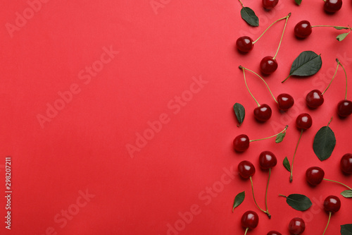 Photographie Tasty ripe cherries with leaves on red background, flat lay