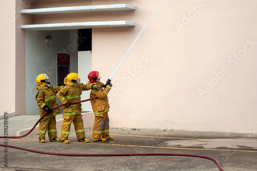 Stampa su Tela Firefighter aim inject water into the building by the hoses to quench the fire