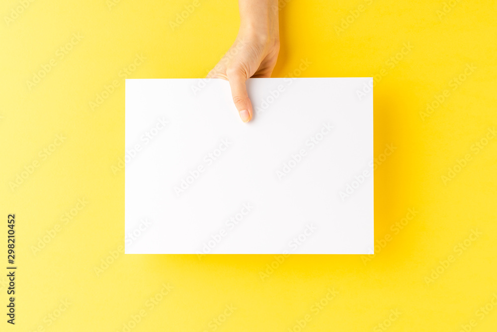 Fototapety, obrazy: Woman's hand showing blank a4 paper sheet on yellow background. Close up