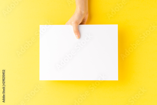 Woman's hand showing blank a4 paper sheet on yellow background Canvas-taulu
