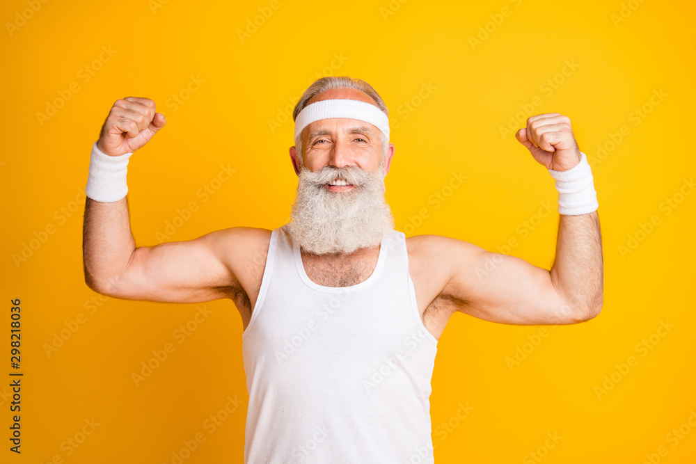 Fototapeta Photo of cheerful positive handsome man smiling toothily showing his muscles demonstrating strength isolated vivid yellow color background