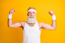Photo Of Cheerful Positive Handsome Man Smiling Toothily Showing His Muscles Demonstrating Strength Isolated Vivid Yellow Color Background
