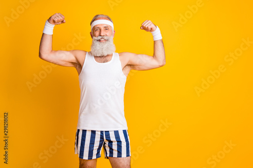 Fotografía  Photo of handsome cheerful positive man old smiling toothily demonstrating bicep