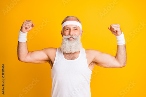 Photo of cheerful positive handsome man smiling toothily showing his muscles dem Fototapeta