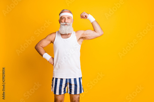 Fotografie, Obraz Photo of cheerful positive attractive handsome old man demonstrating his muscles