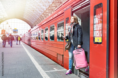 Woman tourist with suitcase coming out of train Canvas
