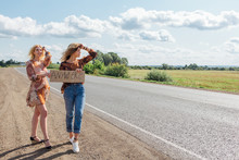 Two Beautiful Girls Hitchhiking And Vote With A Sign ANYWHERE On Road. Copy Space.