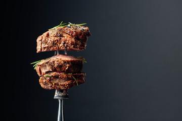 Grilovani goveđi odrezak s ružmarinom na crnoj podlozi.