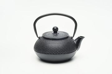 Black cast iron teapot on a white background.