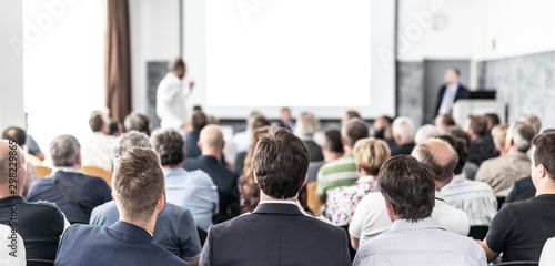 I have a question. Group of business people sitting at the chairs in conference hall. Businessman standing up asking a question. Conference and Presentation. Business and Entrepreneurship. - 298229865