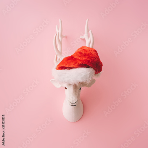 Christmas reindeer decoration with Santas hat and pink background. Minimal creative concept.