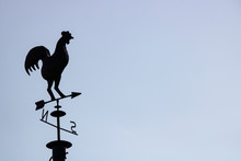 Wind Rooster Silhouette On Metallic Roof