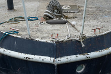 Front, Detailed View Of A Weathered Fishing Trawler Showing Its Rough Deck Texture. Also In View Is The Ships Anchor Chain And Single Porthole In The Hull.