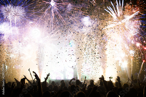 Photo  Stage lights and crowd of audience with hands raised at a music festival
