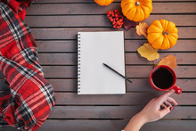Planing To Do List. Autumn Mood Composition On A Wooden Table. Young European Girl With Red Manicure On Nails Holds In Hands Red Cup On Belted Plaid Background, Warming Drink. Cozy Atmosphere