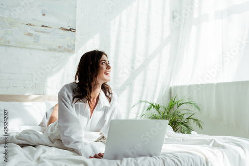 smiling and attractive woman with laptop looking away at morning