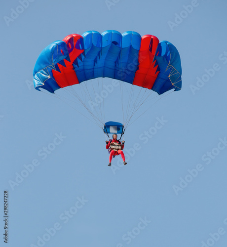 Fotografie, Obraz Red and blue parachute with paratrooper in sky