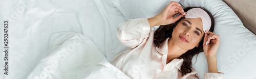 Obraz panoramic shot of attractive woman with sleeping mask looking at camera at morning - fototapety do salonu