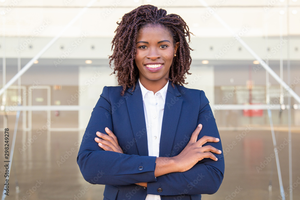 Fototapeta Happy successful business leader posing near outside. Young business woman with arms folded standing near glass wall, looking at camera, smiling. African American businesswoman concept