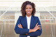 Happy successful business leader posing near outside. Young business woman with arms folded standing near glass wall, looking at camera, smiling. African American businesswoman concept
