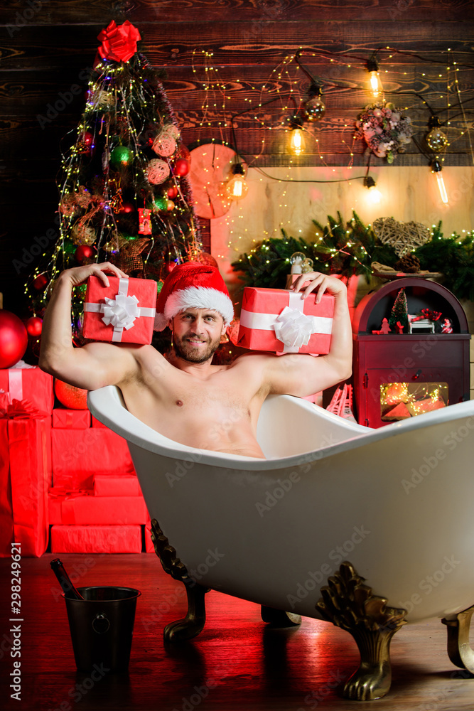 Fototapeta her own santa. sexy mature man bath. winter holidays. happy new year gift. erotic wish. feel temptation. winter decorations background. muscular man relax bathtub. best xmas present. christmas spa