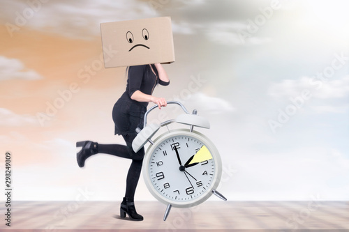 Woman with big clock in hand is running against time change