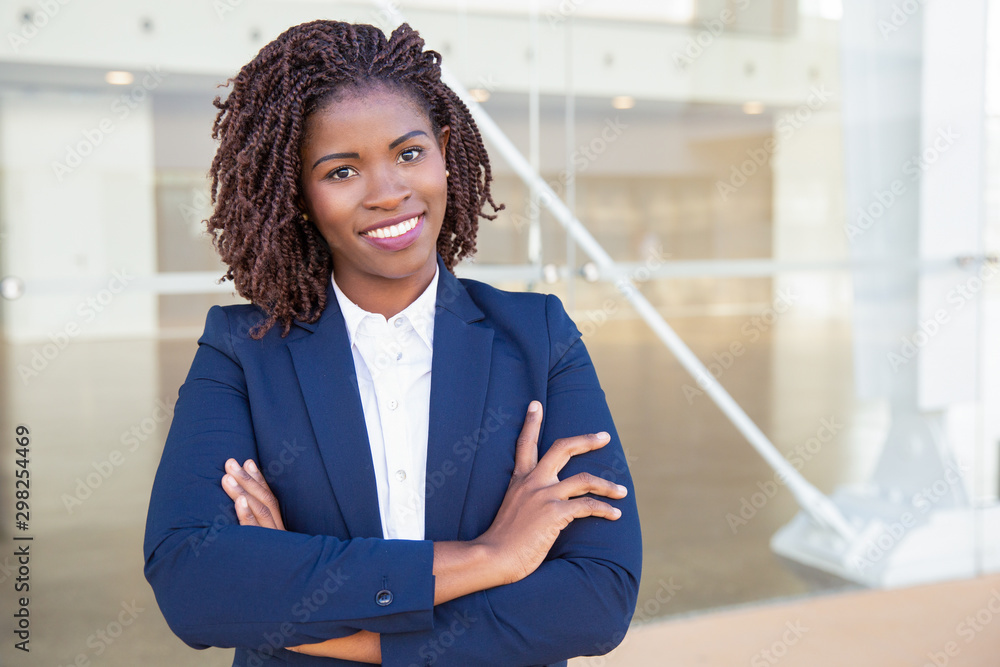 Fototapeta Happy successful professional posing near office building. Young African American business woman with arms folded standing outside, looking at camera, smiling. Female business leader concept