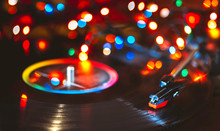 Vinyl Record Close-up On A Background Of Bright Christmas Lights, Selective Focus, Bokeh.