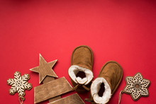 Baby Winter Christmas Red Background With Boots , Wood Tree And Showflakes. Child Holiday, Copy Space
