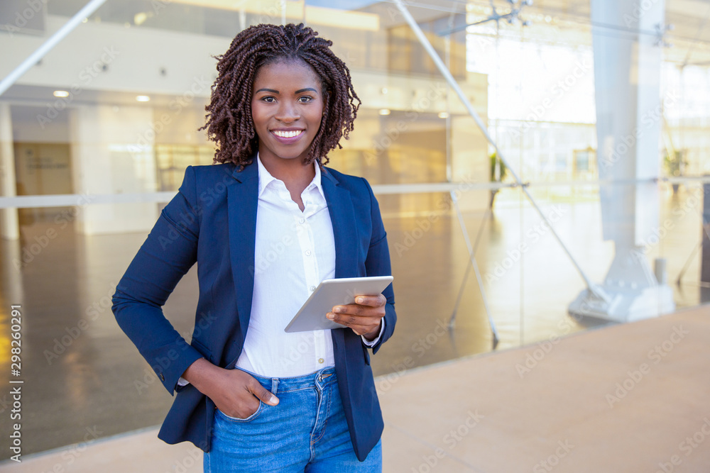 Fototapeta Happy professional using tablet near office building. Young African American business woman standing outside, holding digital device, looking at camera, smiling. Wi-Fi concept