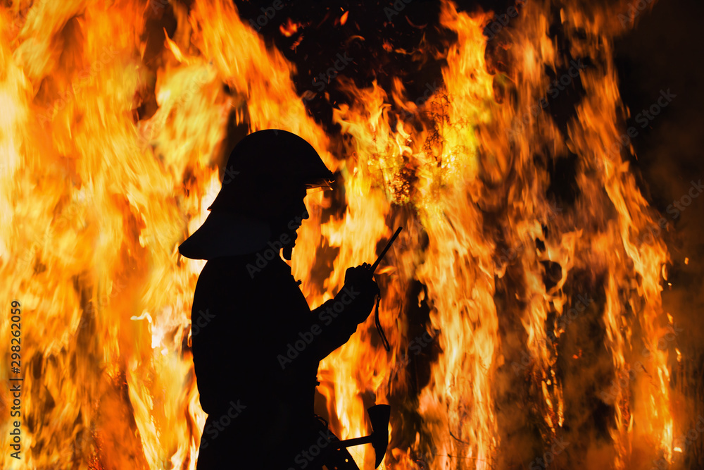 Fototapety, obrazy: silhouette firefighter on background fire at night