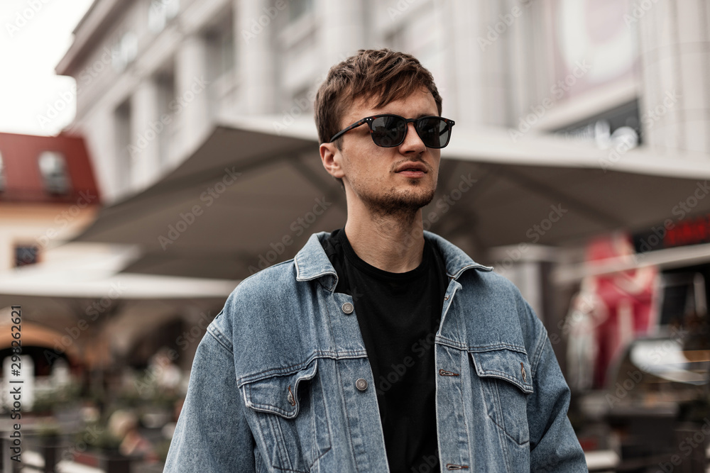 Fototapety, obrazy: Cool nice young hipster man in a fashionable blue denim jacket in sunglasses stands on the street in the city. Handsome guy model with a stylish hairstyle rests outdoors. Fashion spring menswear.