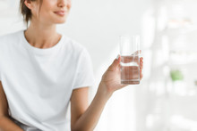 Cropped View Of Smiling Girl Holding Glass Of Water In The Morning