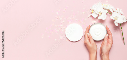 Orchidée Young woman holding a opened container with cosmetic cream lotion body milk White Phalaenopsis orchid flowers festive confetti on pink background Flat lay top view minimalism style Beauty concept