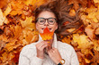 canvas print picture - Happy pretty young woman with a cute smile in a glasses in a sweater with a maple leaf in hands lies on golden foliage. Cheerful girl enjoys relaxes outdoors on a warm autumn day. View from above.