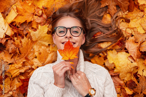 Fotografie, Obraz  Happy pretty young woman with a cute smile in a glasses in a sweater with a maple leaf in hands lies on golden foliage