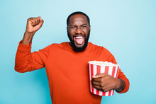 Photo Of Cheerful Overjoyed Ecstatic Crazy Man Screaming In Happiness Holding Pop Corn Bucket With Emotional Facial Expression In Orange Sweater Isolated Vivid Blue Color Background