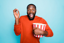 Photo Of Funny Atonished Mixed-race Crazy Ecstatic Screaming Man Watching Television Series And Amazed About Plot Holding Popcorn Bucket Smiling Toothily Isolated Blue Vivid Color Background