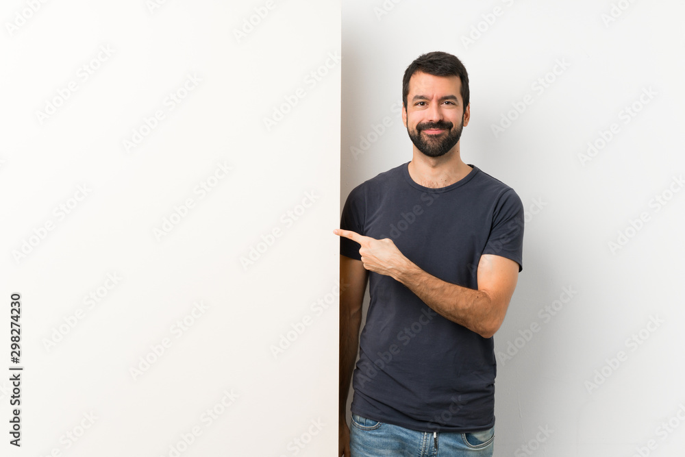 Fototapeta Young handsome man with beard holding a big empty placard pointing to the side to present a product