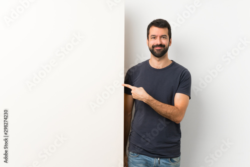 Young handsome man with beard holding a big empty placard pointing to the side to present a product