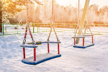 Bright Playground In The Snow On A Sunny Winter Day. Children's Swing Swing On A Winter Playground Covered With Snow. Colorful Play Set For Children's Entertainment After The Winter Snowfall