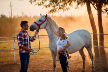 Smiling Family In A Horse Farm Petting Horses