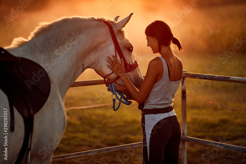 Girl with hourse. Woman and her horse on a sunset. Fotobehang