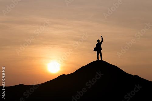 Fototapeta Silhouette of businessman raising his hand to celebrate success on top of mountain, White background. obraz na płótnie