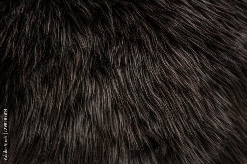 Foto abstract background of warm artificial dark brown fur on a knitted base close up