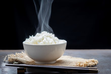Cooked Rice With Steam In Black Bowl On Dark Background,hot Cooked Rice In Bowl Selective Focus,hot Food And Healthy