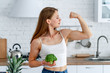 Leinwandbild Motiv Strong woman with broccoli in the kitchen. Young healthy girl shows her strong hands.
