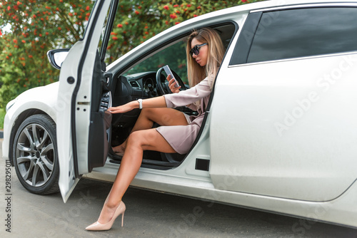 plakat Beautiful girl business lady, summer autumn city, gets out car, getting car tanned leather shoes. Car rental, car sharing. Car parking, business meeting city. Mobile phone, call reads writes message.