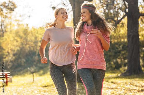 Spoed Foto op Canvas Jogging Two female friends jogging at the city park.Autumn season.